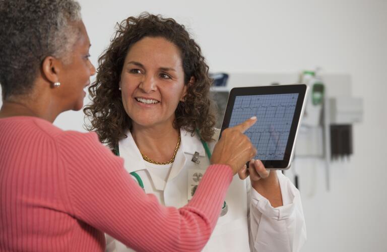 Doctor showing patient ekg test result on digital tablet