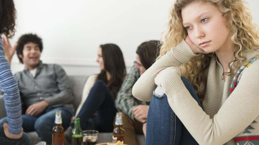 Young Caucasian girl looking lonely with group of friends in background