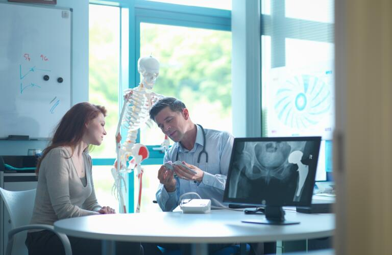 Young female Caucasian woman talking to male Caucasian doctor about artificial hip joint
