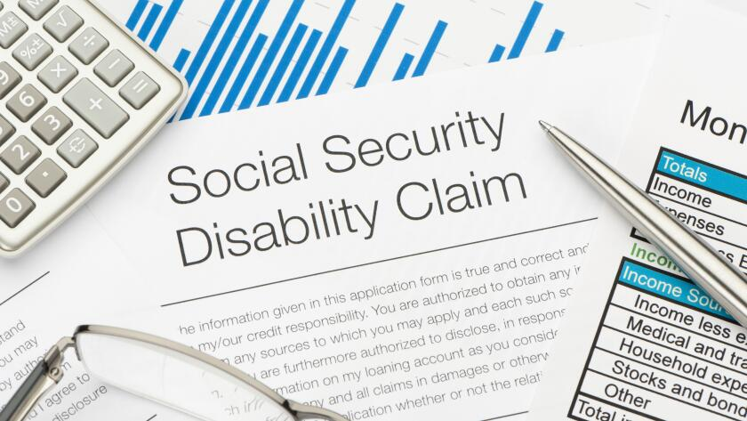 social security disability claim with calculator glass and pen
