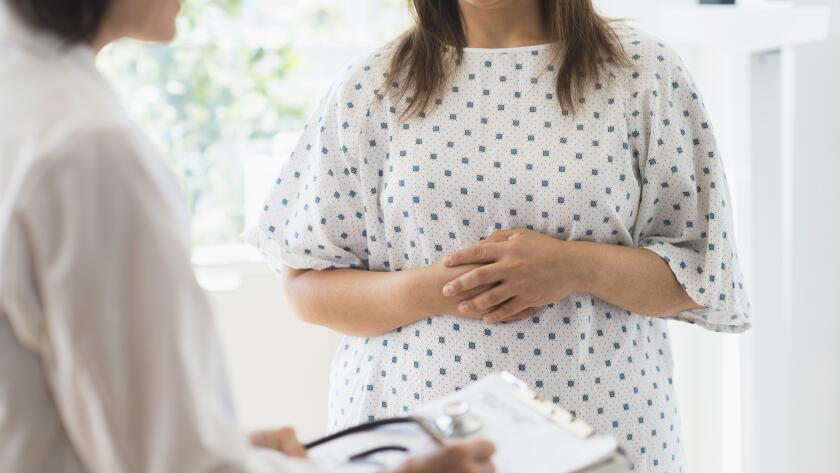 woman-in-patient-gown-listening-to-doctor