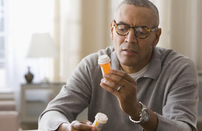 man-holding-two-bottles-of-pills