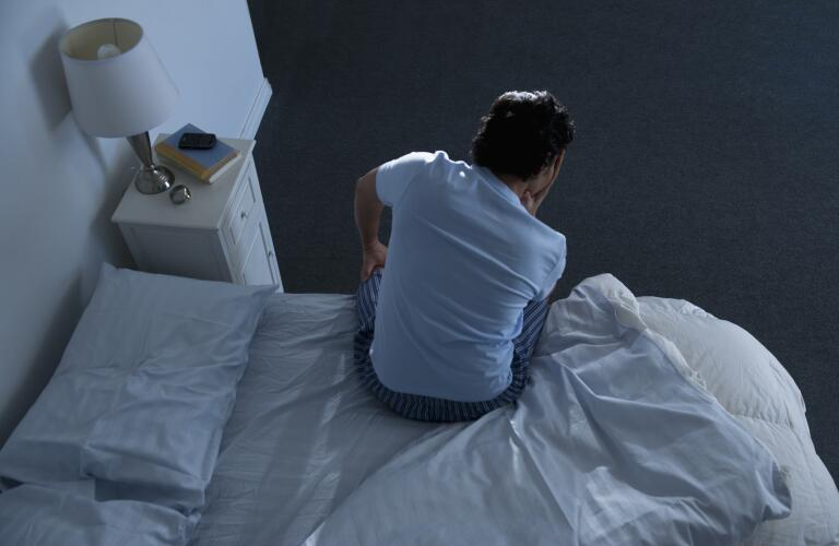 man in low light sitting up in bed with head in hand