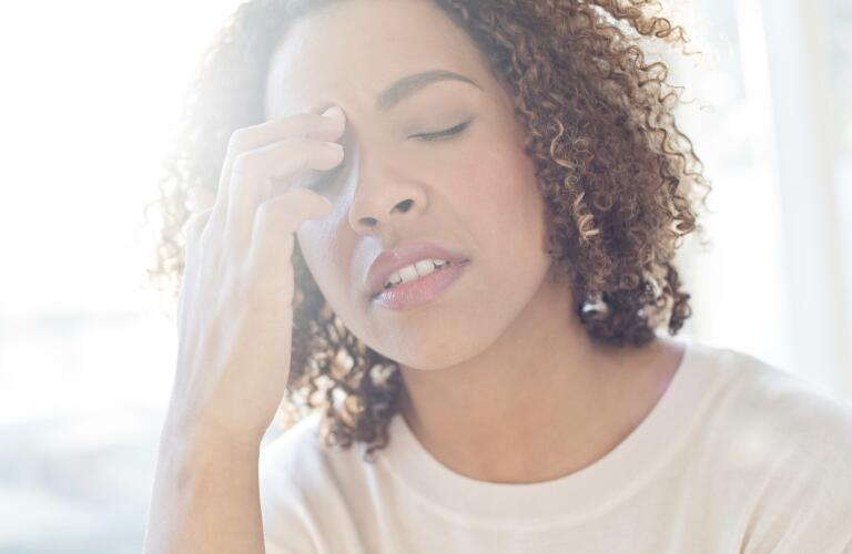 Young African American woman looking stressed holding hand to forehead with eyes closed