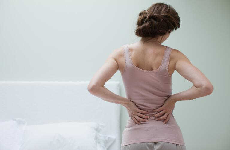 woman-in-bedroom-with-back-pain