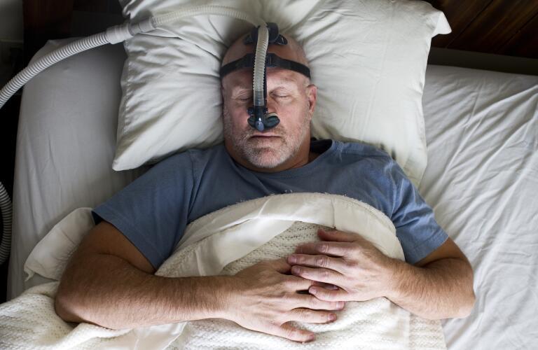 man sleeping in bed wearing cpap mask