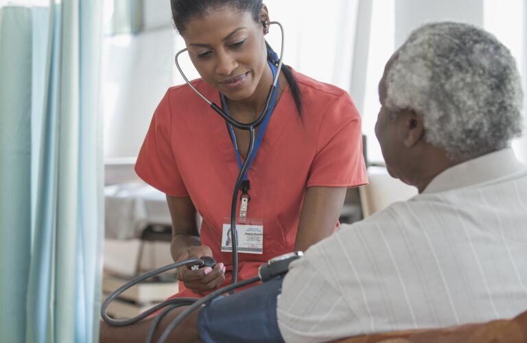 Caregiver taking blood pressure of older man in wheelchair