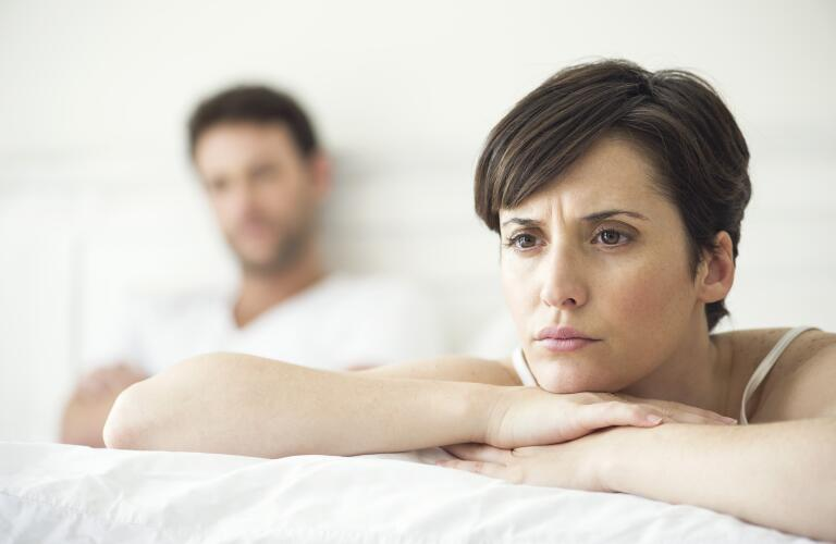Caucasian couple in bed with woman looking concerned over lack of libido, emotional issues or painful sex
