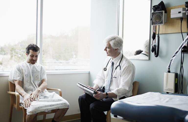 Male doctor in discussion with male patient in exam room