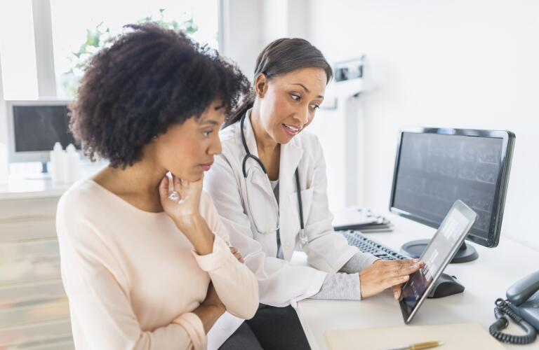 doctor talking to patient and pointing to screen