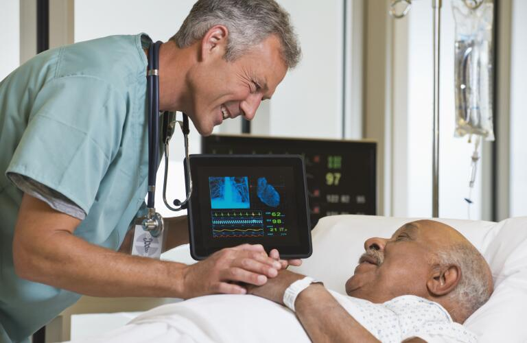 Middle age Caucasian male doctor smiling and talking to older African American male patient in hospital bed