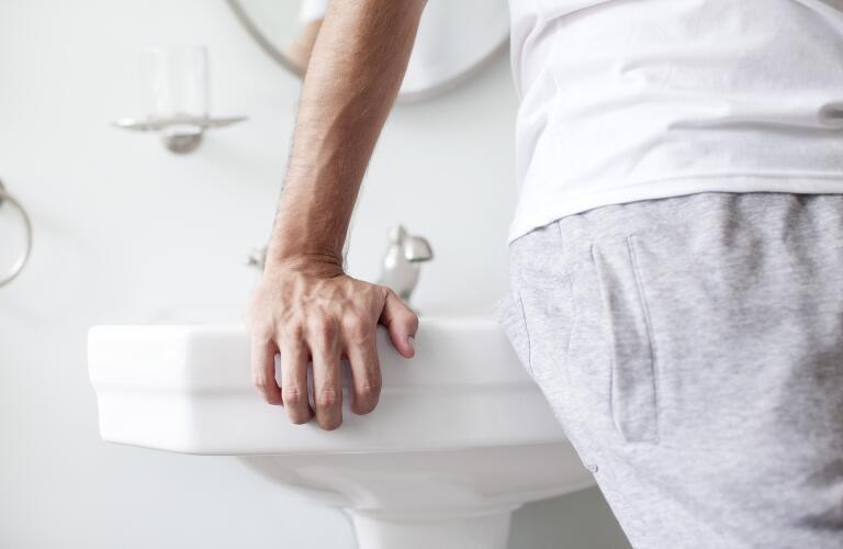 man leaning against sink in bathroom