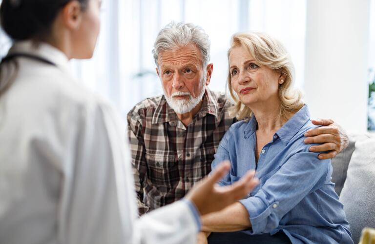 Mature couple talking to their doctor during her home visit.