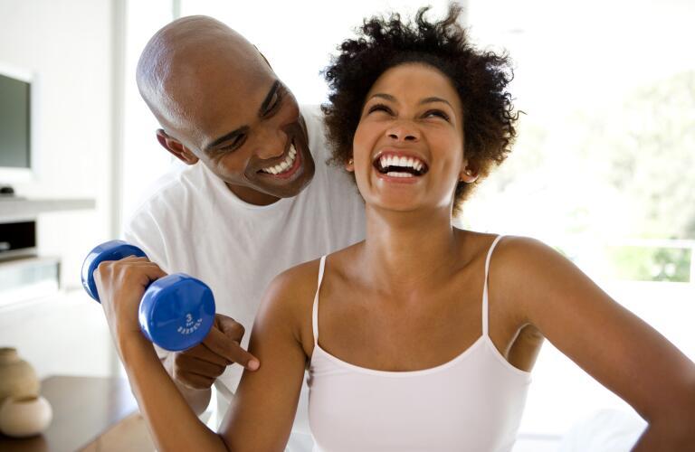 Man smiling at woman lifting weights