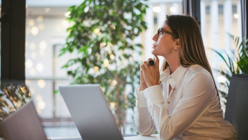Caucasian businesswoman thinking at desk in office