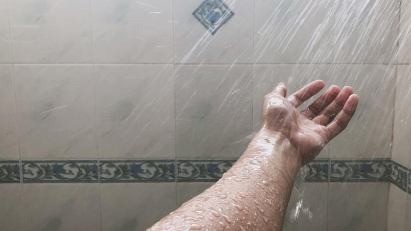 water spraying on hand in shower