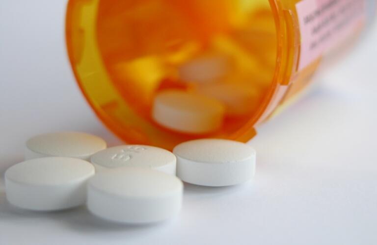 White pills spill from medicine bottle