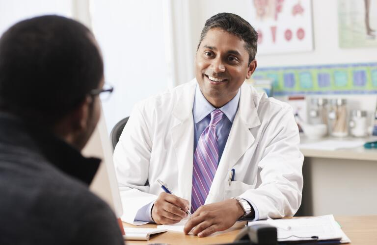 male doctor smiling and talking with male patient in office