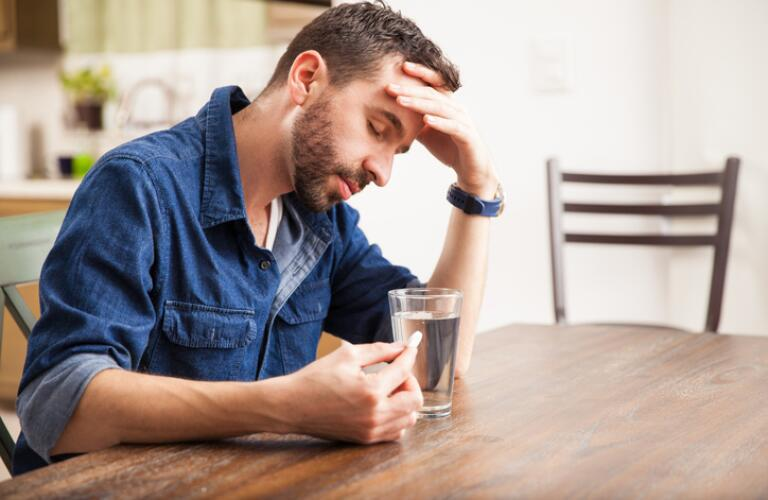 sick-man-sitting-at-table-with-pill-and-glass-of-water