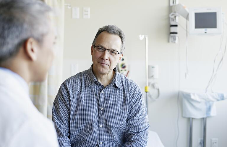 Doctor talking to male patient in hospital room