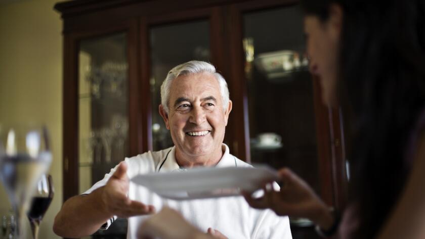 smiling man reaching for dinner plate
