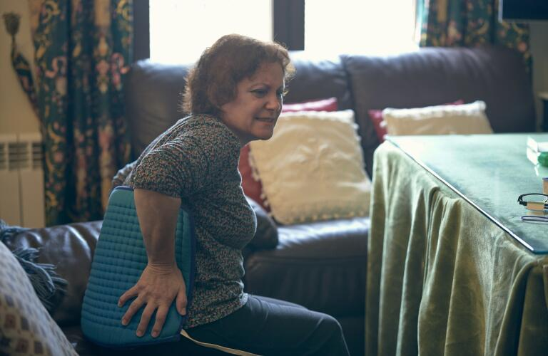 Older woman on couch with heating pad on back
