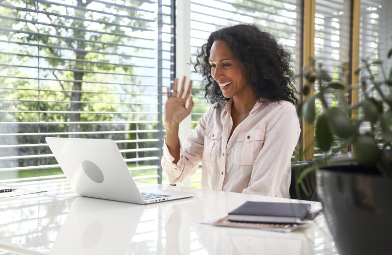 smiling woman waving at laptop in the middle of a video conference call