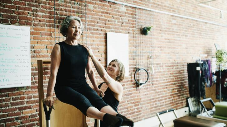 Senior Asian American woman doing pilates in gym with trainer