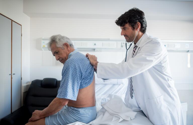 Caucasian male doctor checking breathing of older Caucasian patient with stethoscope on patient's back