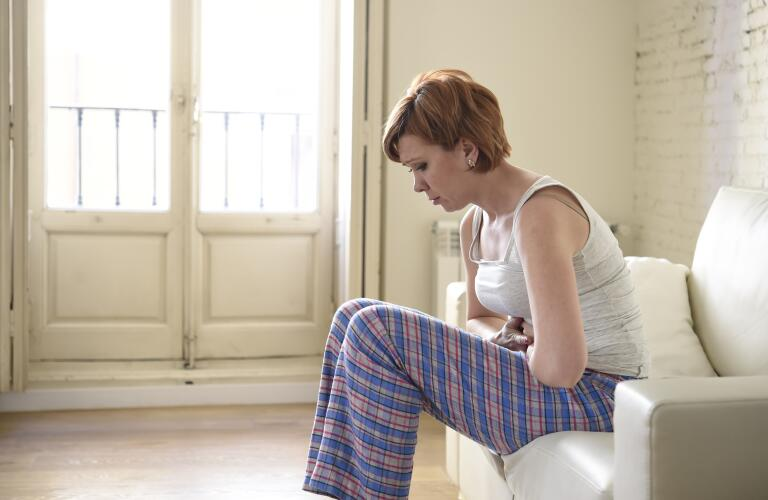 young woman sitting on couching with stomach pain