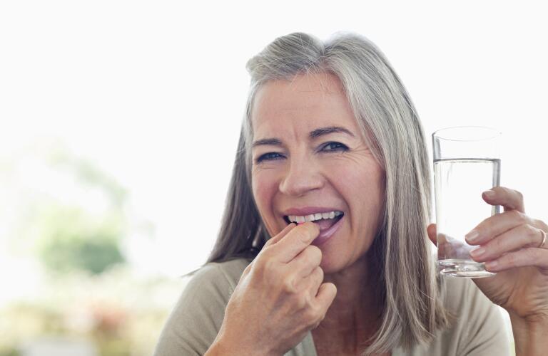 smiling woman taking vitamins