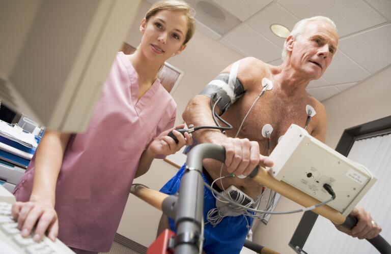 nurse with patient during heart stress test (electrocardiogram)