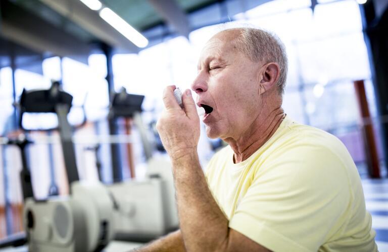 senior man using inhaler while exercising at gym