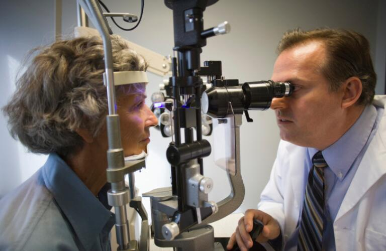 Ophthalmologist checking woman's eyes