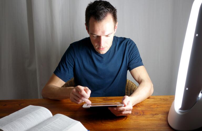 young man looking at digital tablet device near light therapy lamp