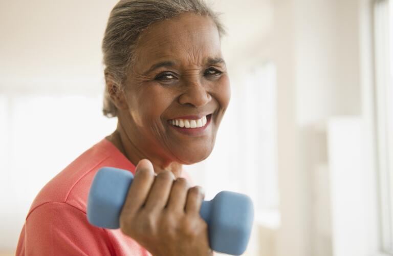 portrait of smiling senior woman lifting hand weight