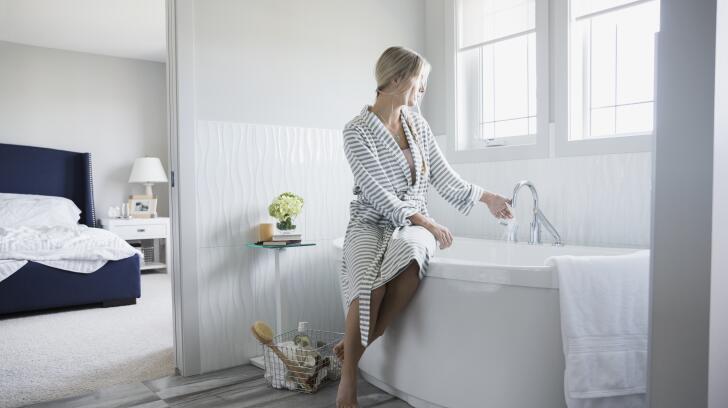 woman in bathrobe filling up bathtub