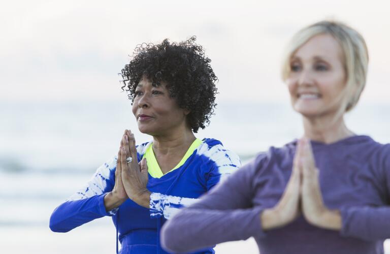Two mature women exercising on beach, doing yoga
