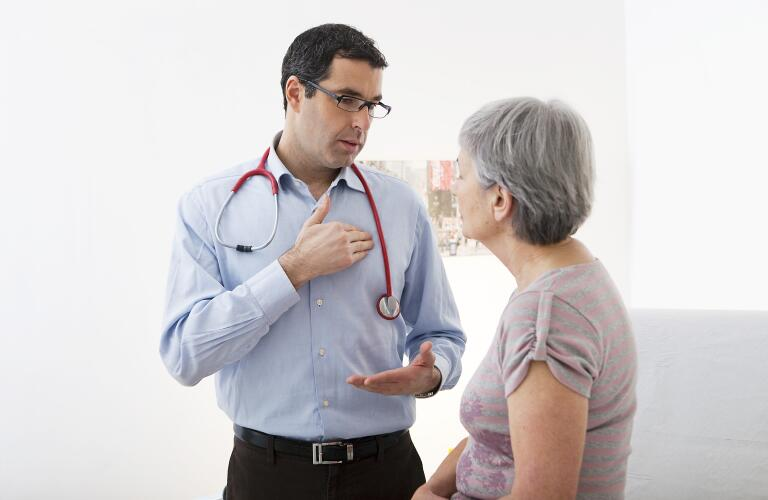 Middle age male Caucasian doctor talking to older female patient about heart or chest pain