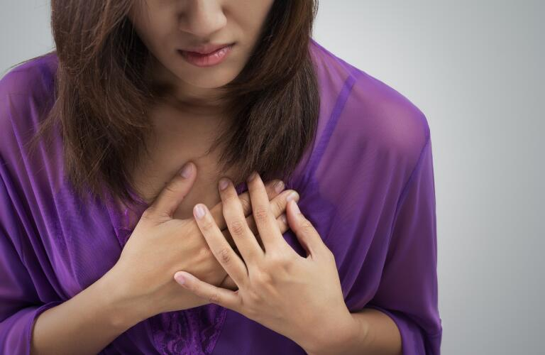 Woman holding chest to indicate heart attack