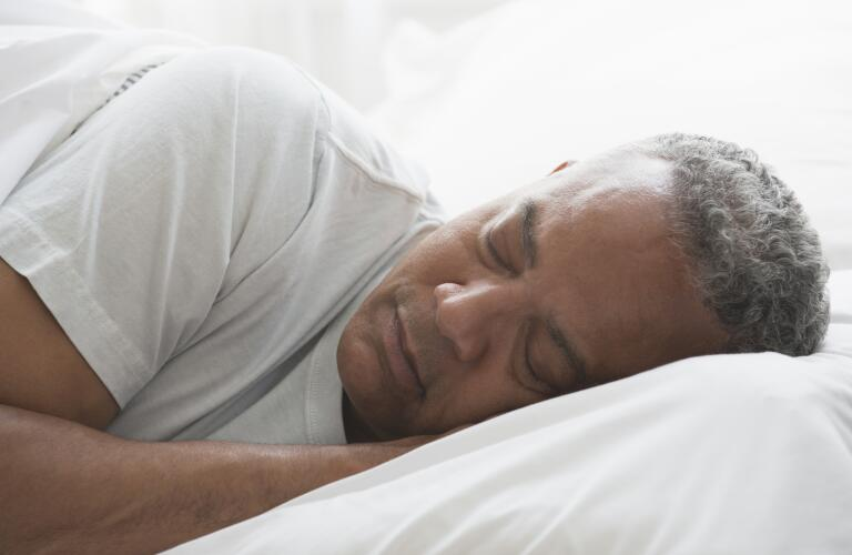 portrait of senior African American male sleeping in bed on side
