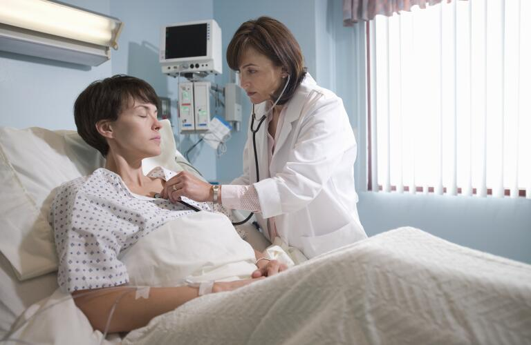 Female doctor at hospital checking female patient's heart with stethoscope