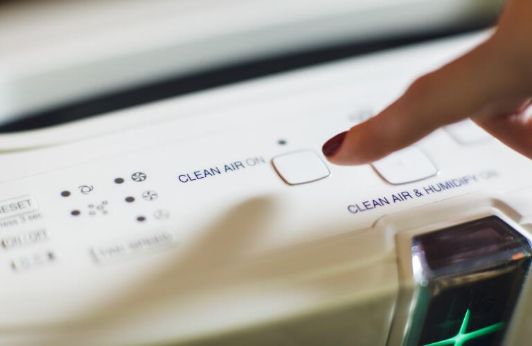 Close-up of woman's finger turning on air purifier power button