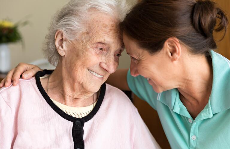 Elderly Caucasian woman smiling while being comforted by younger Caucasian caregiver
