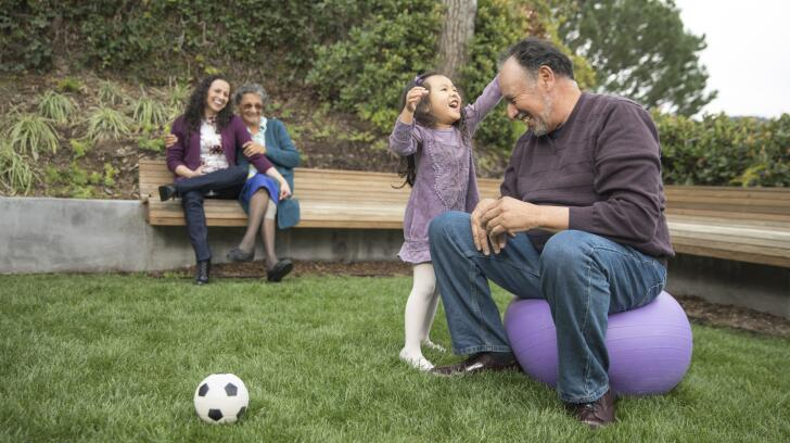 Grandfather playing in park with granddaughter
