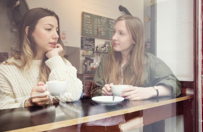 Two young Caucasian women in serious conversation at coffee shop
