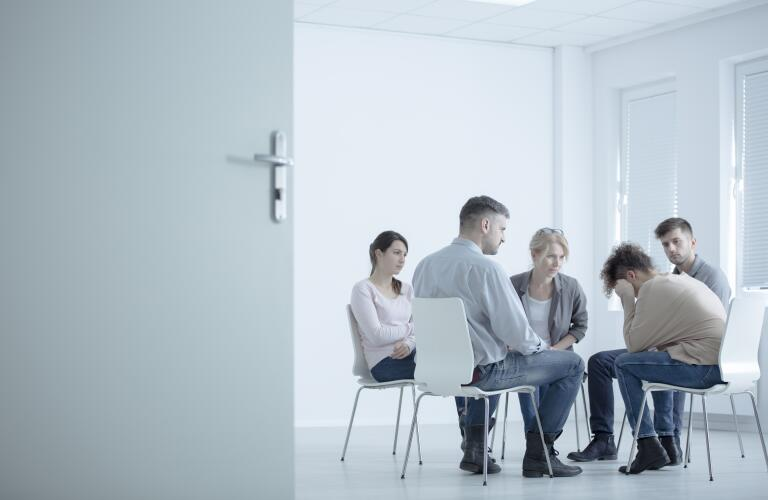 Group of people at group therapy, grief counseling, addiction treatment or substance abuse counseling