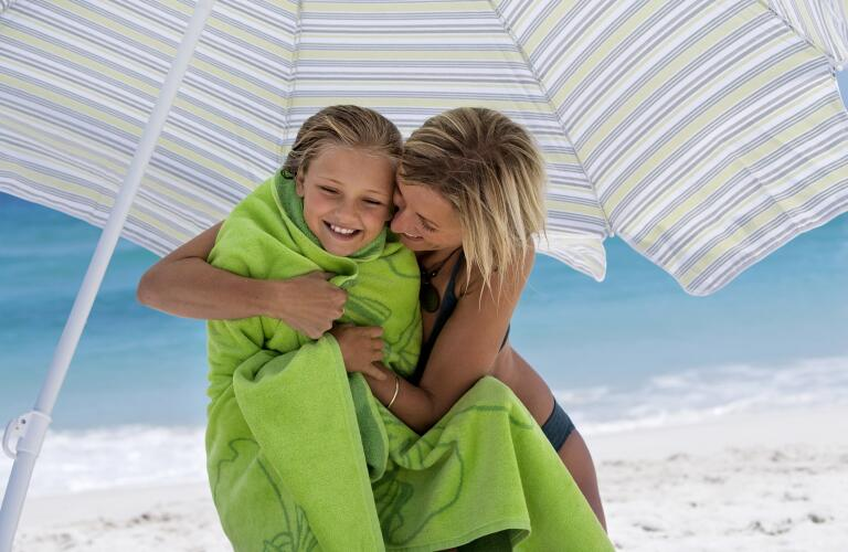 mother embracing daughter under sunshade