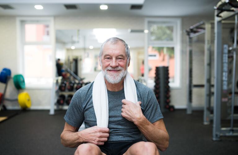 Caucasian senior man in gym smiling during ab exercises