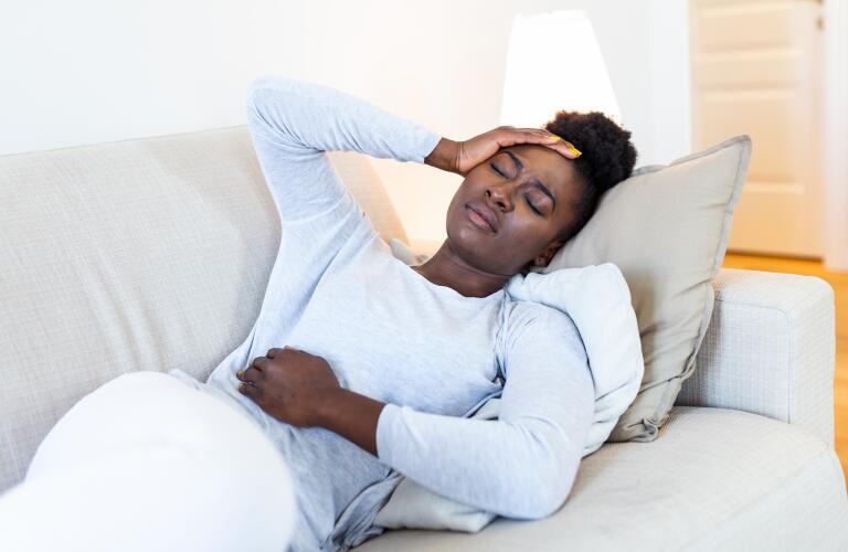 African American woman in pain on couch with hands on head and abdomen